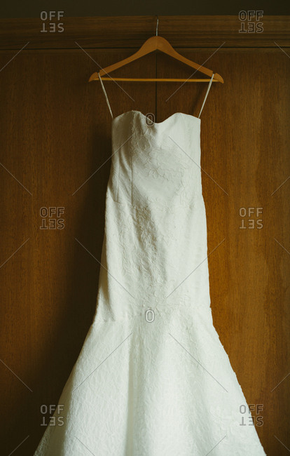 Lace wedding dress hanging in front of closet