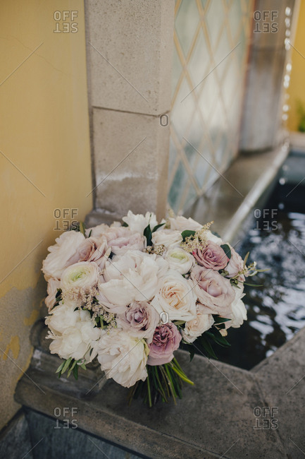 Bouquet of pink and white roses on garden fountain