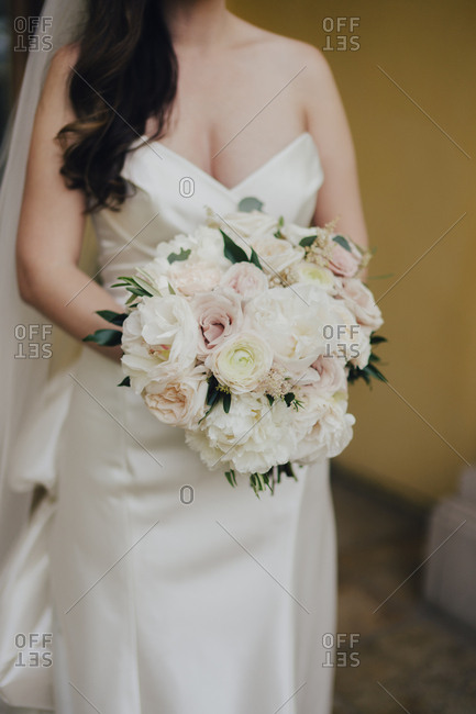 Neck down portrait of bride with bouquet of pink and white roses