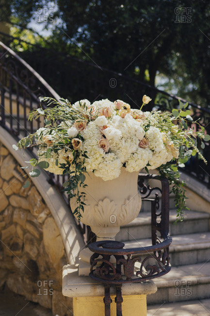 Garden urn filled with arrangement of roses and hydrangeas