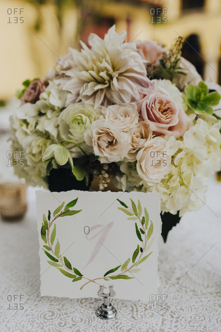 Table number card with floral centerpiece at wedding reception