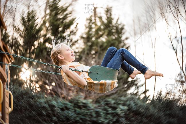 Tween girl swinging barefoot on playground swing