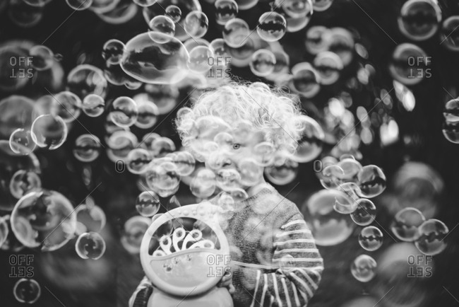 Toddler playing with bubble machine