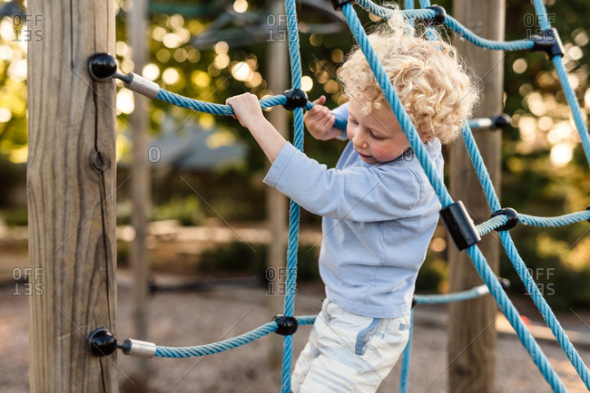 Toddler boy climbing on rope climbing structure