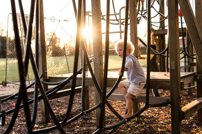 Toddler boy on playground climbing structure at dusk