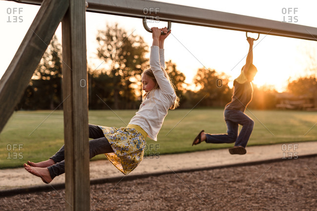Kids playing on playground zip lines at dusk