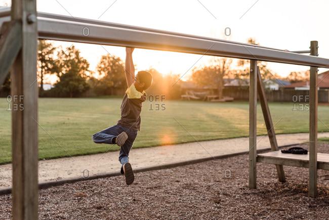 Boy on playground zip line track at dusk