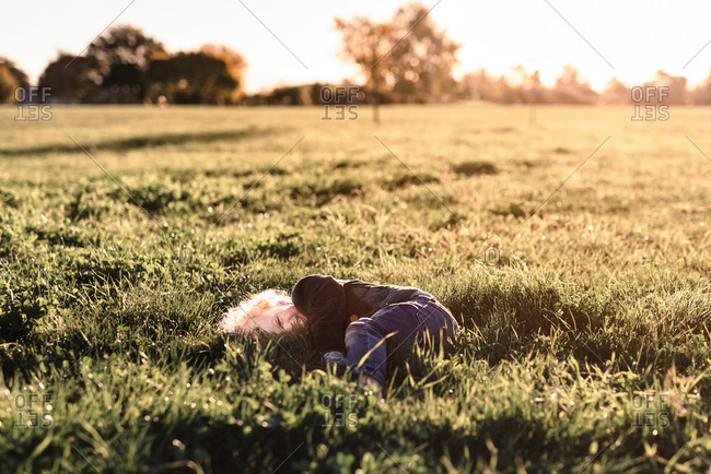 Giggling toddler lying in grass at sunset