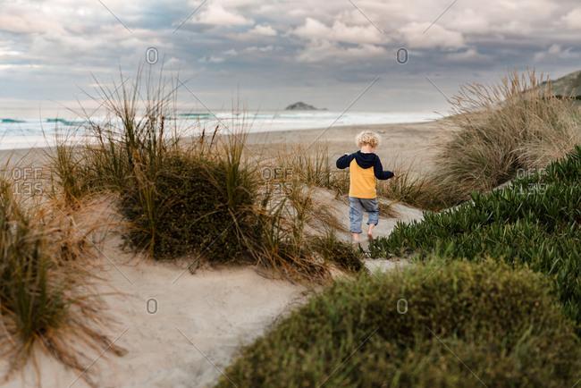 Toddler running on sand dunes at sunset