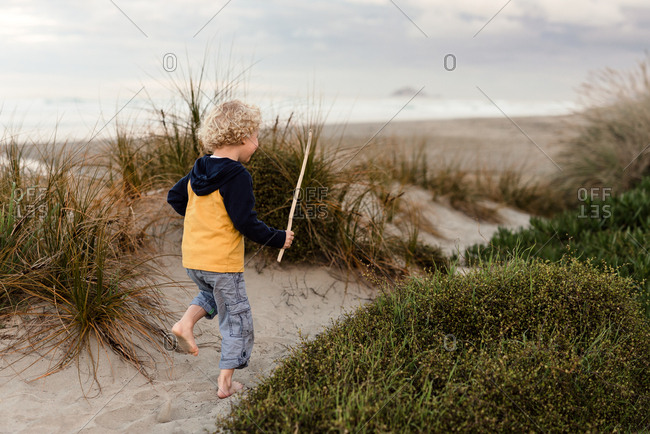 Toddler boy playing with stick on sand dunes