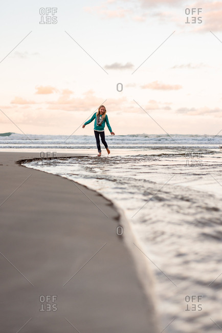 Adolescent girl playing on beach at dusk