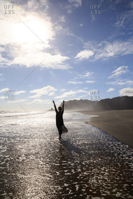 Woman silhouetted wading in ocean