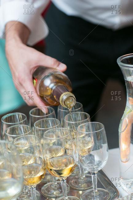 Server filling white wine glasses
