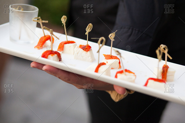 Waiter serving mozzarella appetizer