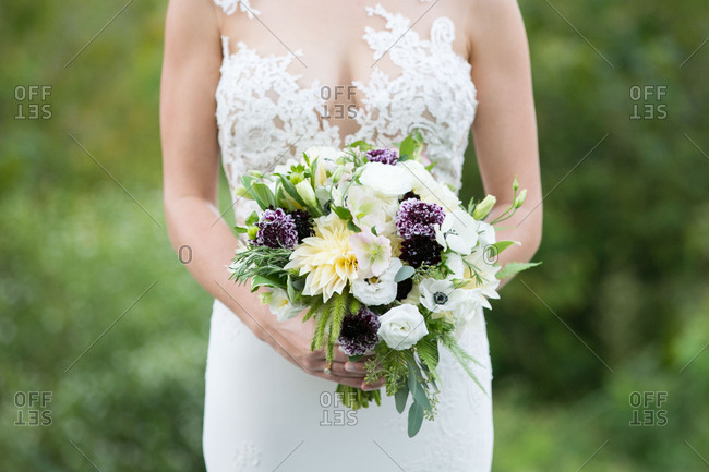 Bride standing outside with floral bouquet