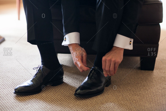 Groom putting on black shoes