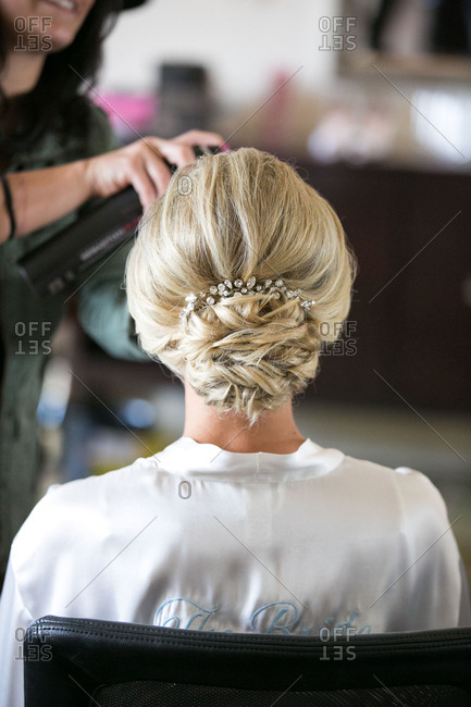 Stylist spraying bride's hair