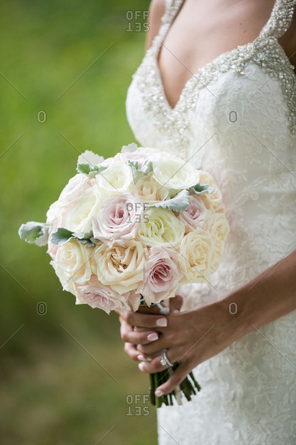 Bride in beaded bodice holding bouquet