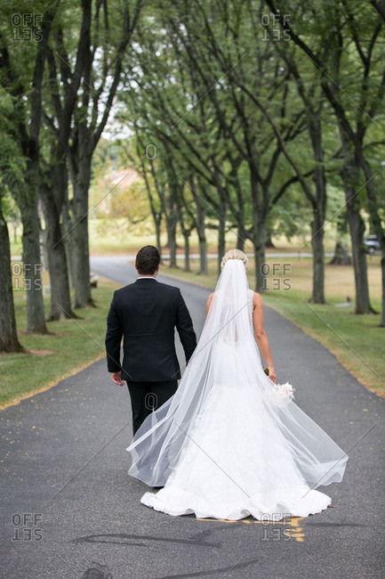 Bridal couple walking down road together