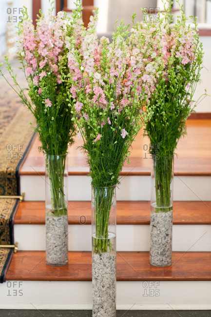 Long stemmed flowers in vases on steps