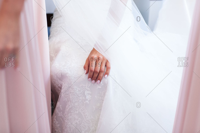 Hand of bride sitting in dress