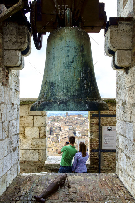 Siena, Italy - May 11, 2014: Couple standing under bell taking picture of Siena from Torre del Mangia tower in Palazzo Publicco palace Tuscany Italy