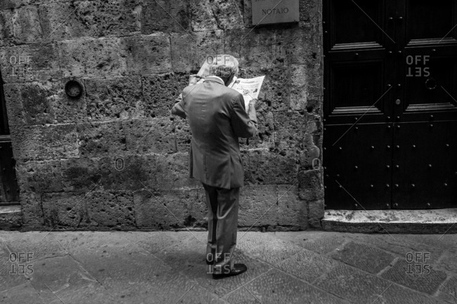 Siena, Italy - May 11, 2014: Man reading the news in the streets of Siena, Italy