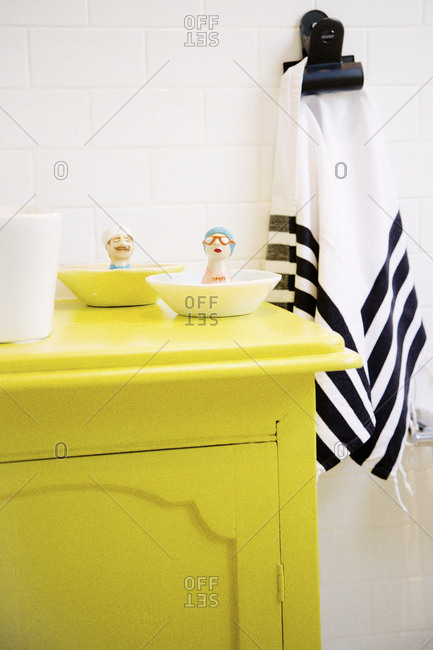 Yellow bathroom vanity with ceramic figures beside the sink