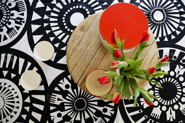 Red tulips on a wooden table with geometric pattern background