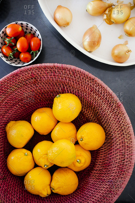 Fresh oranges, onions and tomatoes in bowls