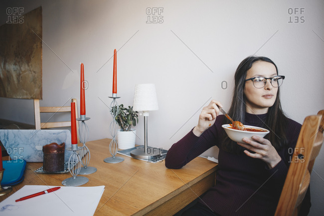 Young woman eating tomato soup sitting on chair by table against wall in dorm