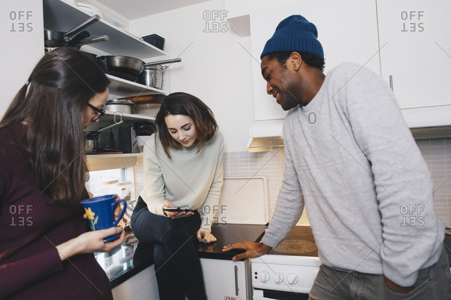 Young woman showing mobile phone to roommates in kitchen
