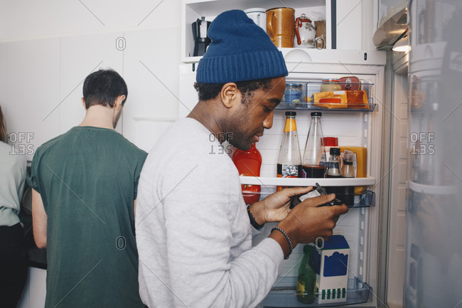 Side view of man looking at food package standing by refrigerator in kitchen