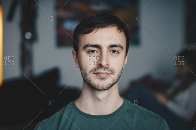 Portrait of young man standing in college dorm room