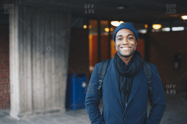 Portrait of happy man wearing blue warm clothing and knit hat standing in campus