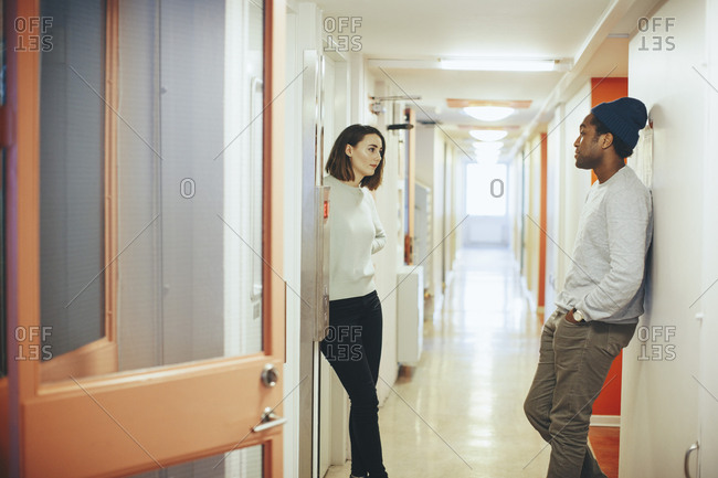 Young friends talking while standing in college dorm corridor