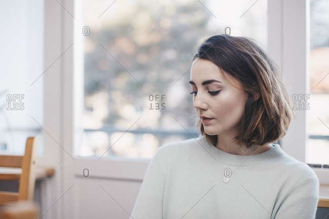 Woman sitting against window at college dorm