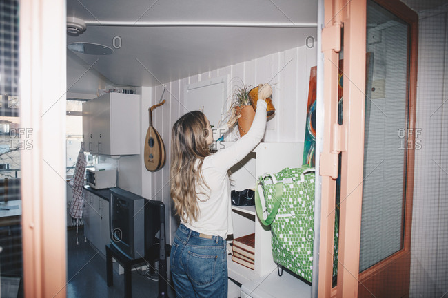 Woman watering potted plant in dorm room
