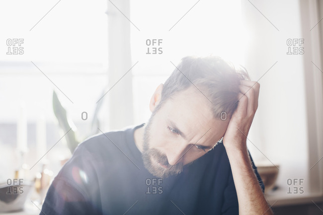 Worried man sitting with head in hands against window at home