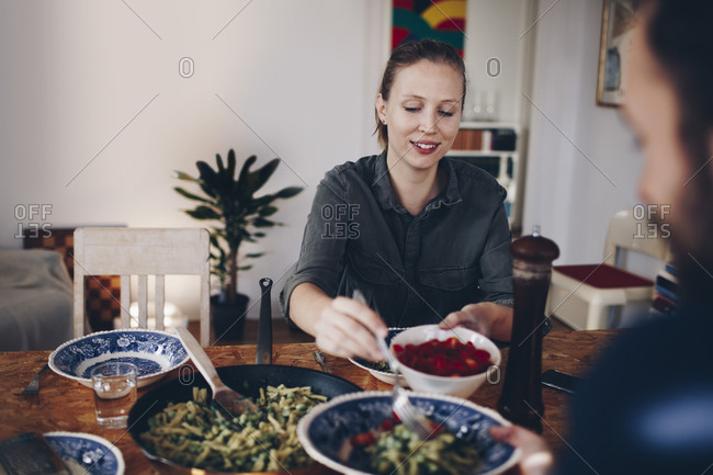 Happy woman serving cherry tomatoes to man in plate at home