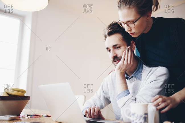 Low angle view of couple looking at laptop in domestic room