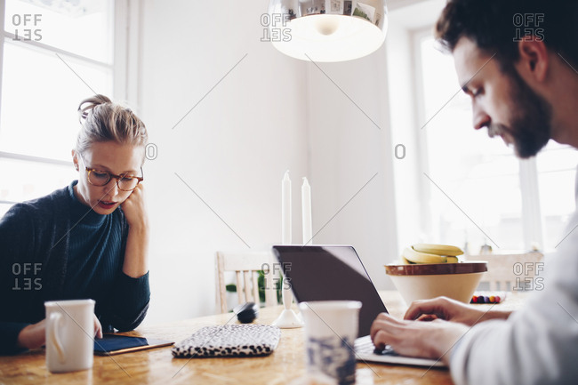 Couple using technologies at dining table while working from home