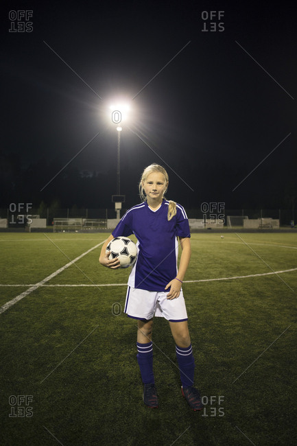 Portrait of confident girl standing holding ball on soccer field against sky at night