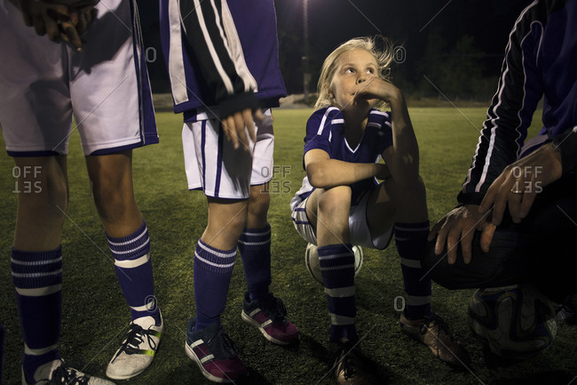 Girl looking at coach explaining strategy on soccer field at night