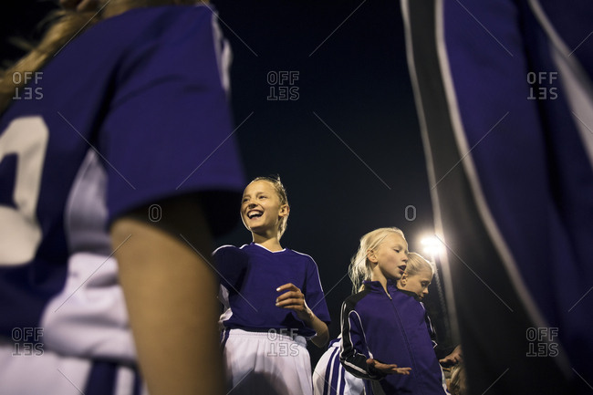 Low angle view of happy athletes standing against sky