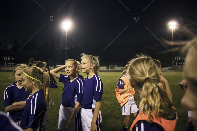 Girls standing on illuminated soccer field against sky at night