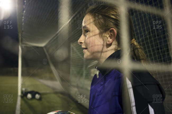 Side view of girl with soccer ball seen through goal post net