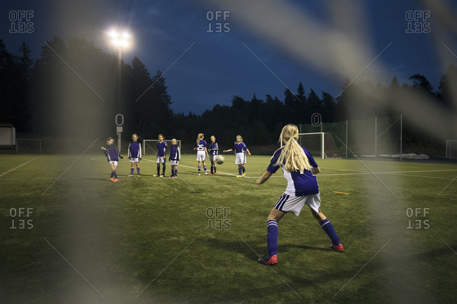 Girls playing soccer seen from goal post net on field against sky