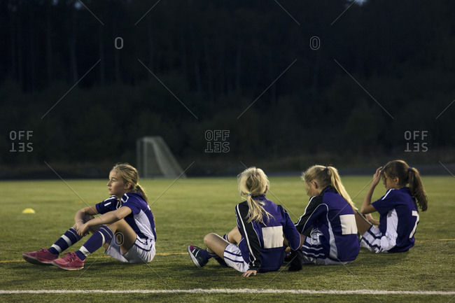 Athletes relaxing on soccer field against trees