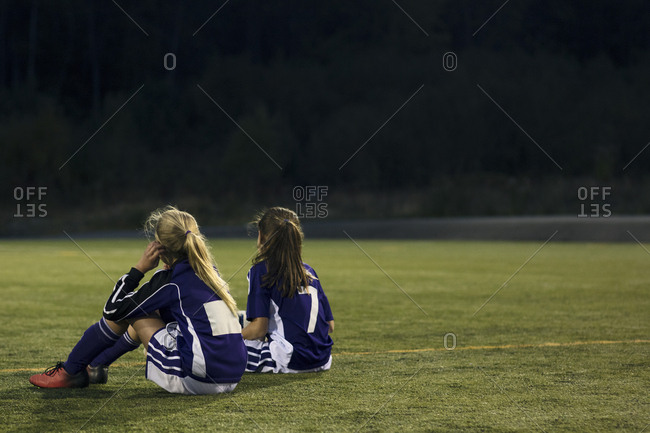 Rear view of girls relaxing on soccer field